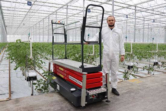 Zdjęcie prezentuje wózek pielęgnacyjno-serwisowy Hortitech 4HD oraz właściciela firmy Mateusza Maryniaczyka w szklarni gdzie w oddali widać sadzonki pomidora w rzędach.